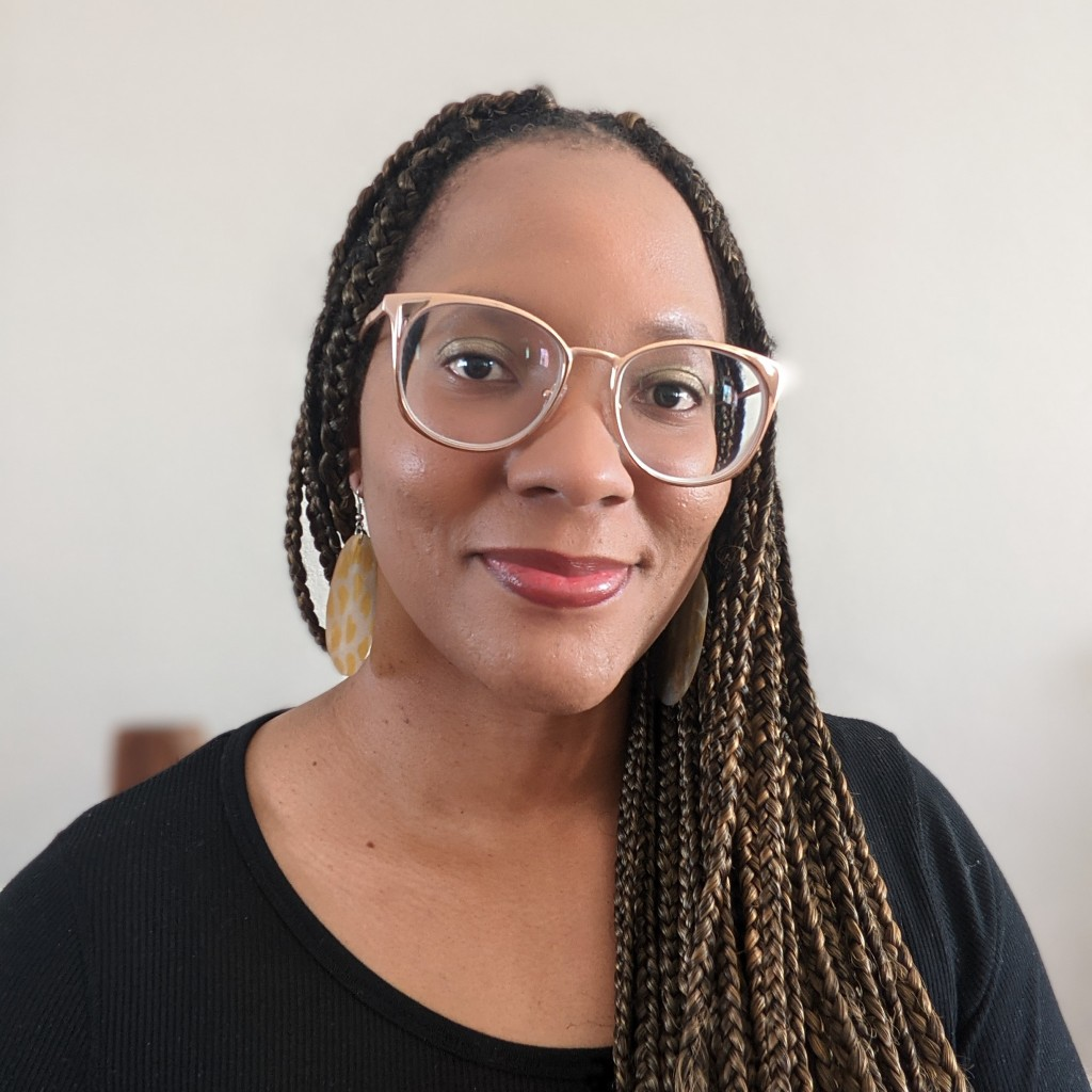 A Black woman wearing rose gold glasses and a black shirt stares at the camera. She has long, skinny braids and circular earrings with yellow hearts printed on them.