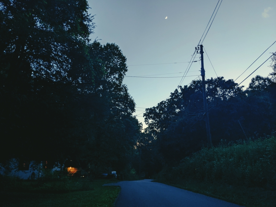 A one-lane road in the blue evening in Tennessee. A crescent moon hangs high in the sky. A porch light shines mid-foreground.